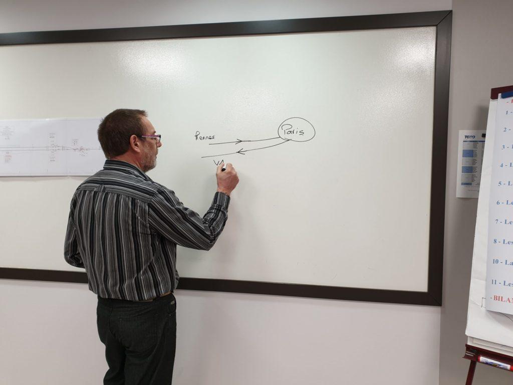 Homme écrit au tableau